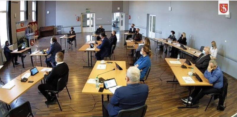 Mężczyźni i kobiety w maseczkach siedzą przy stołach i słuchaja mężczyzny w garniturze, który przemawia z mównicy