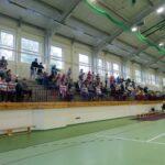 Trybuna z widami w halis sportowej z zieloną podłogą