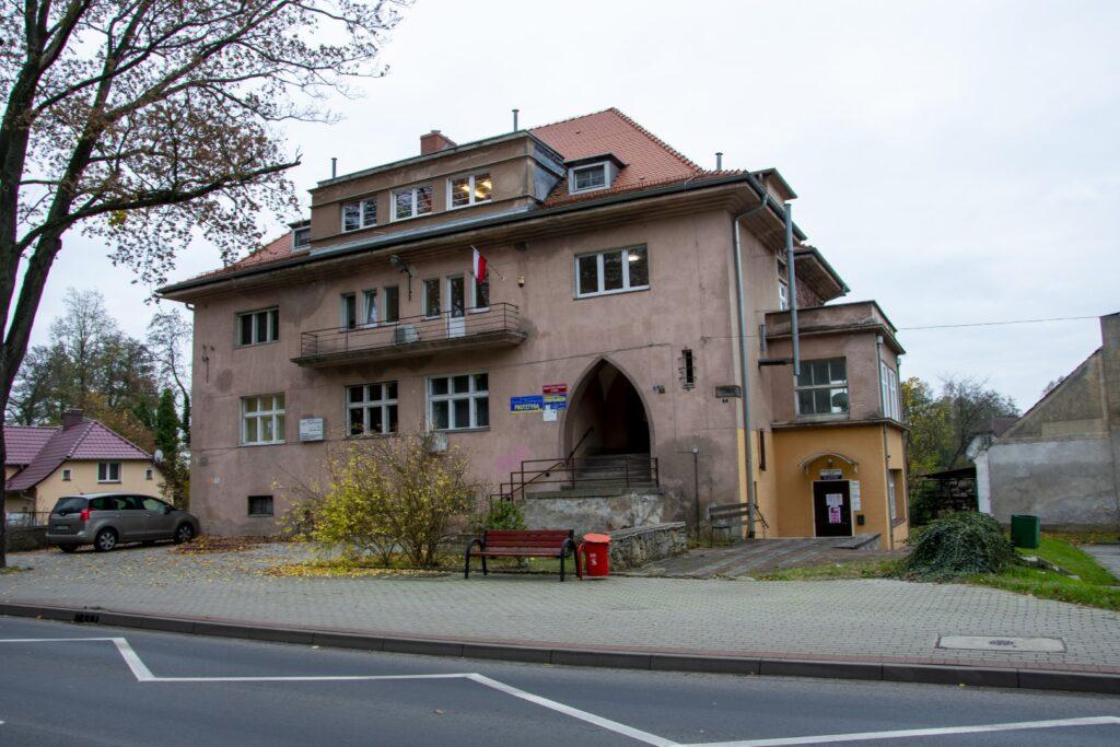 Trzypiętrowy budynek z szara elewacją i sadzistym dachem. Przed budynkiem ławka i czerwony kosz na śmieci