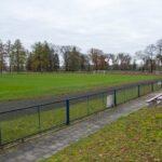 Mały stadion z trawiastym boiskiem i ławkami dla widzów