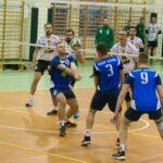 Mecz piłki siatkowej. Atakuja siatkarze w błękitnych koszulkach