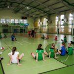 Grupa dziewcząt w sporowych strojach siedzi na podłodze koloru zielonego w hali sportowej