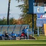 Zadaszone siedziska na stadionie sportowym. Na czterech siedzą mężczyźni w sportowych strojach. Obok wieża z wynikiem meczu
