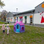 Dwie dziewczynki ubrane w różowe kurtki i czapki idzie po trawniku. W głębi domek dla lalek i parterowy budynek z malunkami na elewacji