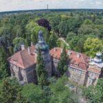Widok z góry na zabytkowy pałac położony wśród drzew