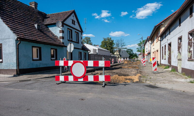 Rozkopana ulica, zagrodzona biało-czerwonymi barierkami i znakiem zakaz ruchu. Po obu stronach ulicy domy