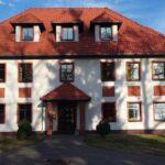 Duzy piętrowy dom z czerwonym spadzistym dachem i oknami dachowymi