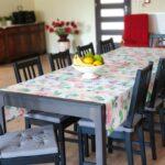 Jadalnia z długim stołem nakrytym kolorowym obrusem. Wokółszare drewniane krzesła