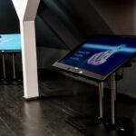 Duże monitory ustawione na aluminiowych nóżkach. Ekrany ustawione są pod kątem. Monitory znajdują się w pomieszczeniu na poddaszu