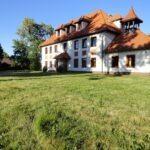Piętrowy dom z dużym czerwonym spadzistym dachem. Przed domem zielony trawnik