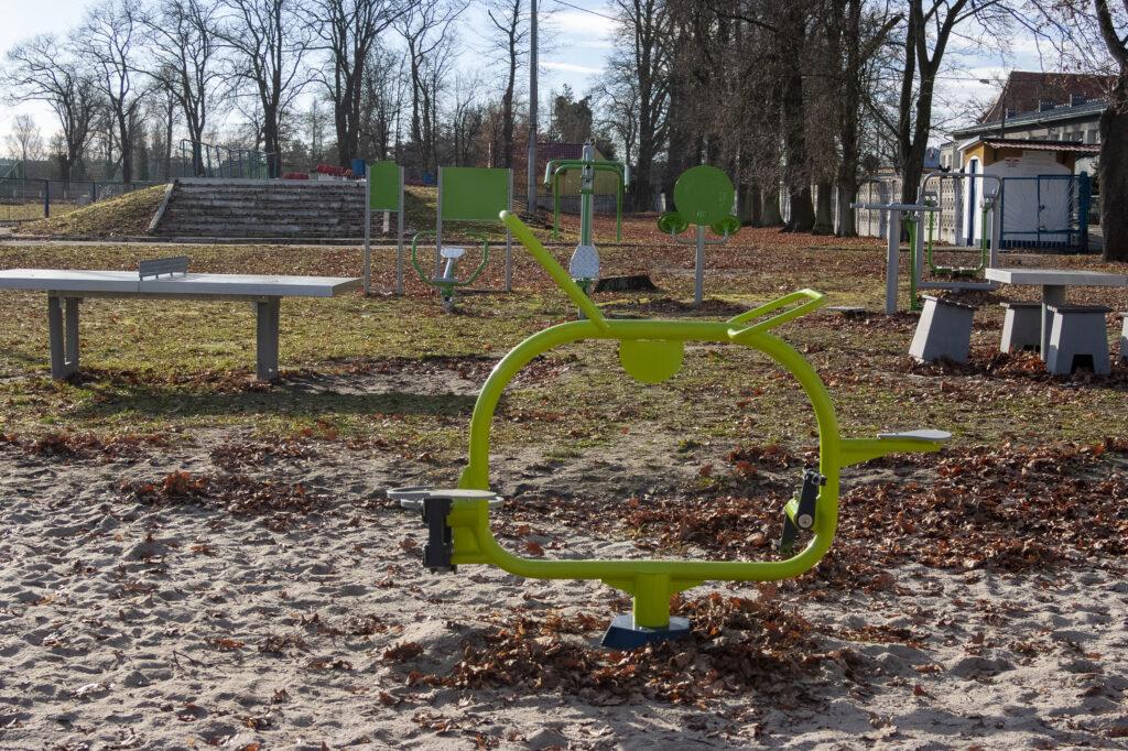 Plac zabaw z nowymi urządzeniami ustawionymi na piaskowym podłożu