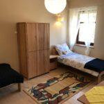 Wnętrze sypialni z dwoma łóżkami, na podłodze kolorowy dywan i drewniana szafa