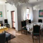 Wnętrze jadalni, stół nakryty obrusem, wokó zielone wyściełane krzesła. Na suficie fantazyjne białe lampy