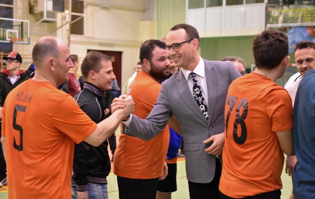 Mężczyzna w jasnej marynarce, krawacie i okularach gratuluje mężczyźnie w pomarańczowej sportowej koszulce