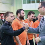Mężczyzna w jasnej marynarce, krawacie i okularach gratuluje niskiemu mężczyźnie w granatowym dresie
