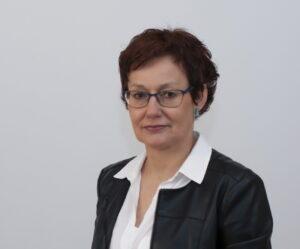 Kobieta brunetka w okularach, białej bluzce i czarnym żakiecie