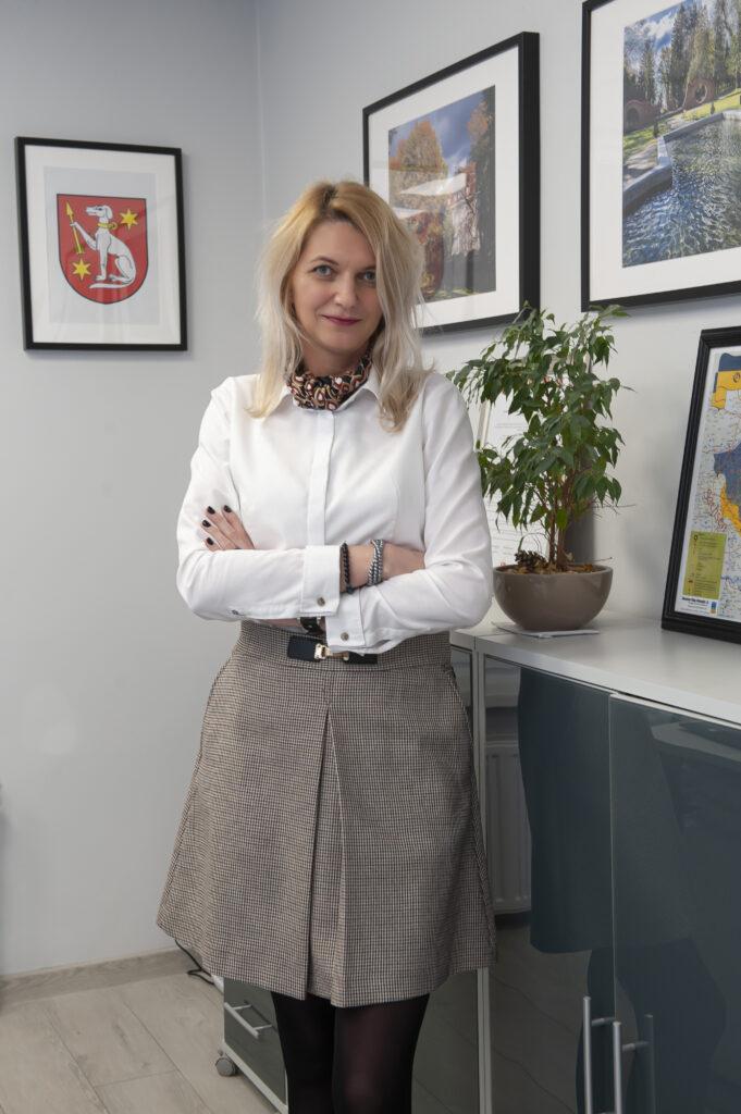 Kobieta z włosami blond, białej bluzce i beżowej spódnicy stoi przy szafce. Na ścianach herb i obrazy