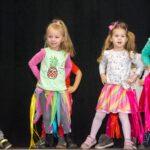 Kolorowo ubrane dzieci tańcza na scenie