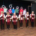 Siedem kobiet ubranych w białe bluzki i czerwone szale trzyma czerwone oprawy