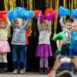 Kolorowo ubrane dzieci podnoszą do góry kolorowe pędzle