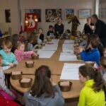 Dzieci siedzą przy długim stole. Przed nimi plastikowe miseczki.