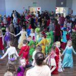 Kolorowo ubrane dzieci tańczą na parkiecie