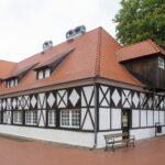 Budynek sztachulcowy czarno-biały z duzym spadzistym czerwonyn dachem