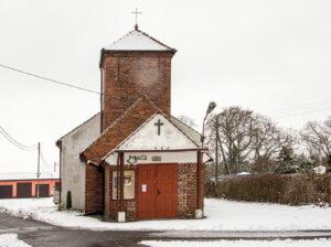 Niewielki kościół z czerwonej cegły z kwadratową wieżą. Fotografia zrobiona zimą.