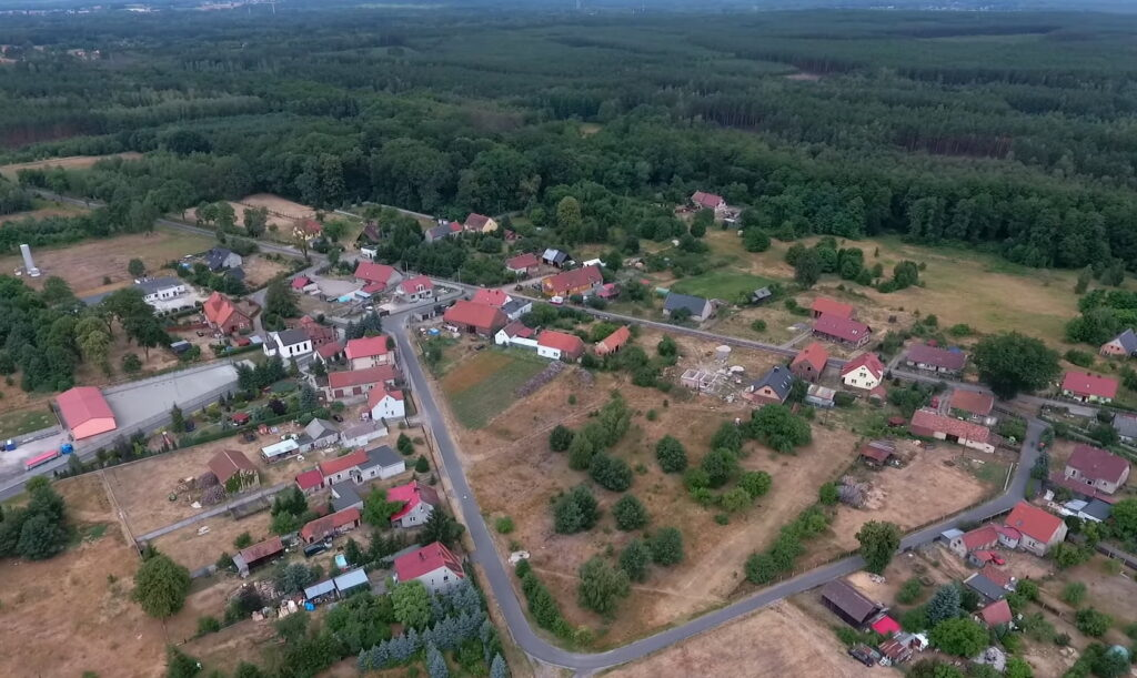 Zdęcie wsi z lotu ptaka. W dali duży las