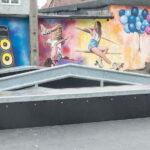 Urządzenie do jazdy na deskorolce. W tle kolorowy mural na ścianie budynku