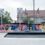 Plac do jazdy na deskorolkach. W tle kolorowy mural na ścianie budynku