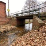 Most przez wąską rzeczką. Z tyłu mur z czerownej cegły