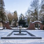 Ośniezony ogród zimowa porą. Z tyłu zabytkowa budowla