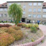 Trzypiętrowy budynek koloru szarego z dużymi oknami. Przed budynkiem klomb z drzewkiem i krzakami. Przy budynku stoją ludzie i rowery