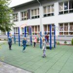Grupa dzieci bawi sie na placu zabaw. W głębi budynk szkolny koloru biało-szarego