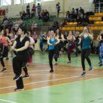 Grupa kobiet w strojch sportowych ćwiczy w hali sportowej