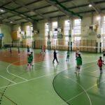 Grpa dziwwcząt w sportowych strojach ćwiczy w hali z zieloną podłogą i dużymi oknami