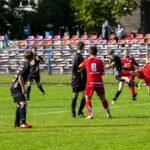 Pilkarze w czarnych i czerwonych strojach podczas meczu piłki nożnej