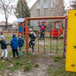 Grupa dzieci ubrana w kolrowe kurtki i czapki bawi się na zewnętrznym placu zabaw
