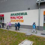 """Grupa dzieci w kurtkach i czapkach idze wzdłuż budynku z napisem """"Akademia małych zuchów"""""""