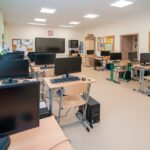 Sala szkolna, a wnije stoły z krzesłami. Na stołach duże monitory, a na podłodze przy stołach stoja komputery