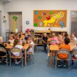 Grupa dzieci siedzi przy czeterch stołach i je posiłek