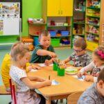 Grupa dzieci siedzi przy stoliku i rysuje. W głębi kolorowe półki z zabawakmi
