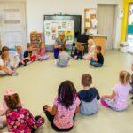 Grupa dzieci siedzi w kręgu na podłodze i patrzy się na kobietę w długich blond włosach