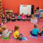 Grupa dzieci siedzi w kręgu na podłodze i patrzy się na kobietę w ciemnych włosach