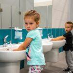 Dziewczynka i chłopiec myja ręce w umywalkach
