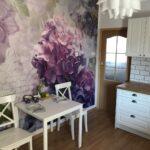 Wnętrze kuchni z białym stolikiem i dwoma białymi krzesłami. W tle kolorowa ściana z kwiatowym wzorem