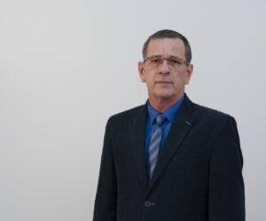 Mężczyzna w średnim wieku w okularach, w niebieskiej koszuli, błękitnym krawacie i czarnej marynarce