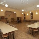 Wnętrze dużej sali z długimi stołami i krzesłami ze srebrnymi oparciami. Z tyłu scena i dwa brązowe piece kaflowe