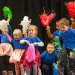 Kolorowe ubrane dzieci machają kolorowymi pędzlami